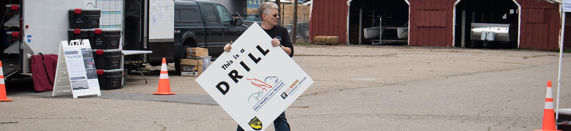 Michael Ziccardi carrying drill sign